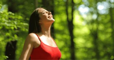 Eine Frau im Wald, die befreit aufatmet