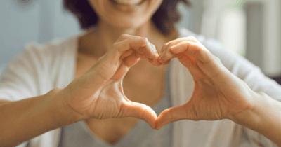 Eine Frau, die mit ihren Händen ein Herz formt
