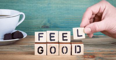 Jemand legt mit Holzbuchstaben die Wörter Feel Good